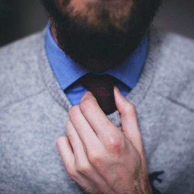 Mann mit Bart der sich seine Krawatte richtet