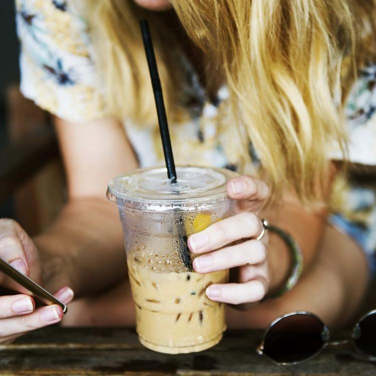 Junge Frau die gerade einen Smoothie genießt und auf Ihrem Smartphone shoppt