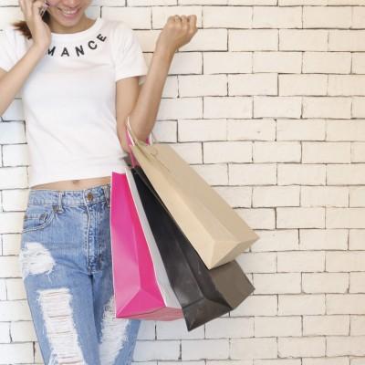 Junge Frau mit vielen Taschen hat Spaß am Onlineshopping