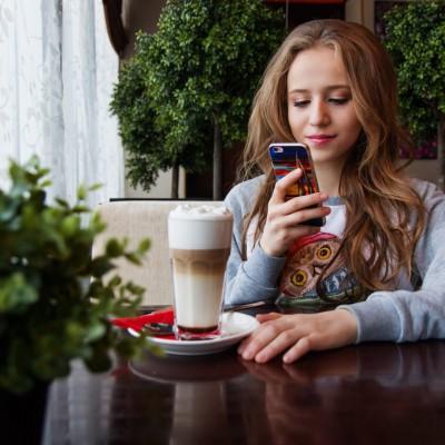 Junge Frau mit einem Latte macchiato shoppt interessiert per Sprachsteuerung mit ihrem Smartphone